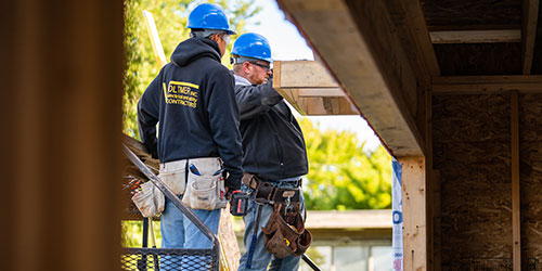 A student and instructor inspect and overhang on a house during construction.