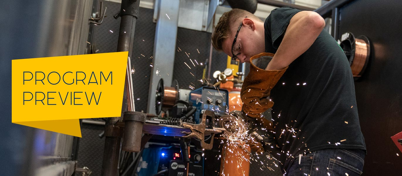 A student uses an angle grinder on a piece of metal in the welding lab.