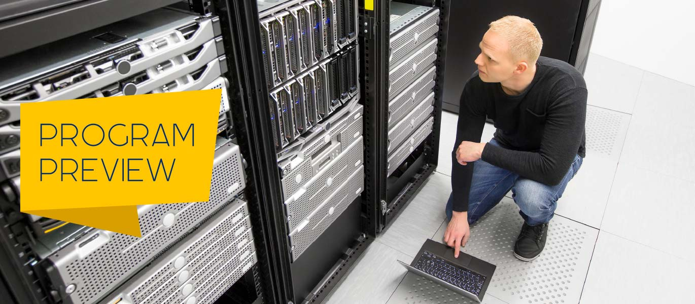 A data center technician inspects a rack of servers.