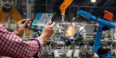 A person controls two manufacturing robots with a tablet.