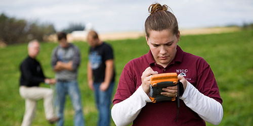 A female NICC student checks a handheld GIS in a field.