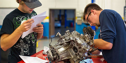 Two male auto tech students rebuild a small engine in the auto lab.