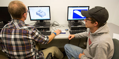 Two CAD students work on a design on a computer.