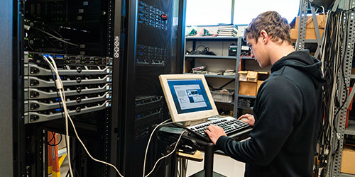 An NICC network student installs a new server in a rack.