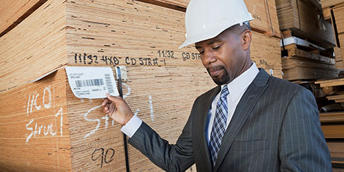 A construction manager checks a delivery tag for a stack of plywood.