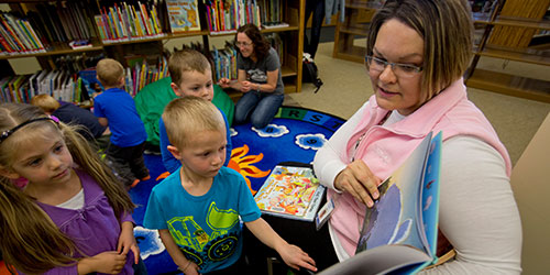 An early childhood instructor reads to children in the library.