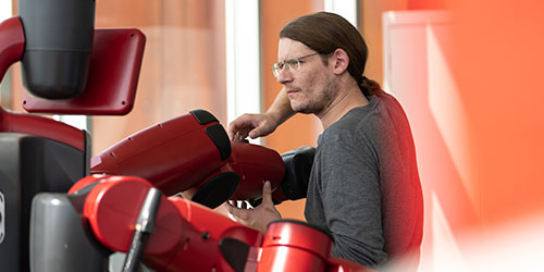 An engineering tech student works on a robot in the industrial tech building.