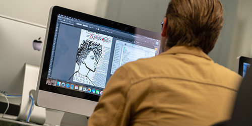 An NICC graphic design student designs a poster in the business lab.