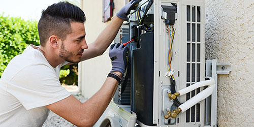 A tech works on an air conditioning unit on a house.