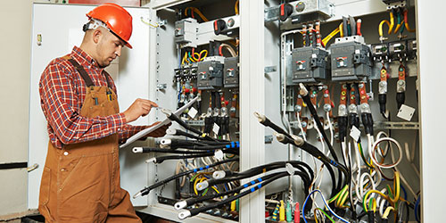 An electrician works on a large power panel in an industrial building.