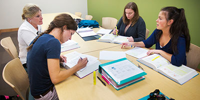 A group of four female students work together in a study room.