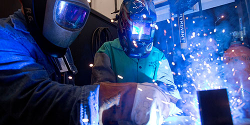 Two welding students practice in the lab.